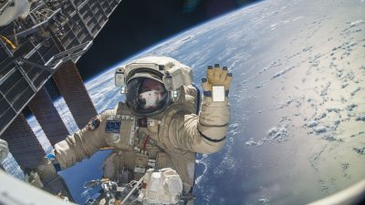 Image: Astronaut on space walk orbiting earth and waving at the camera