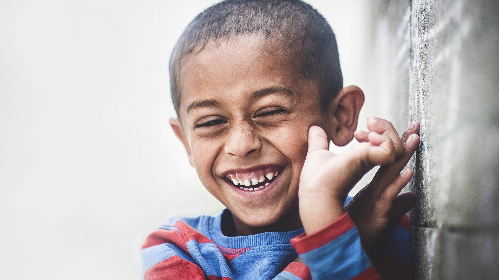 Image: Boy in a striped shirt smiling. Smiling is a facial expression, example of one of the universal expressions of emotion.