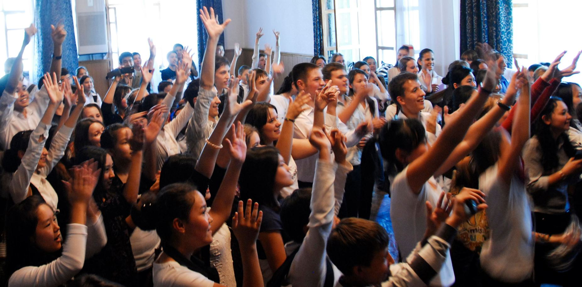 Image: Teenage students raising their hands enthusiastically.