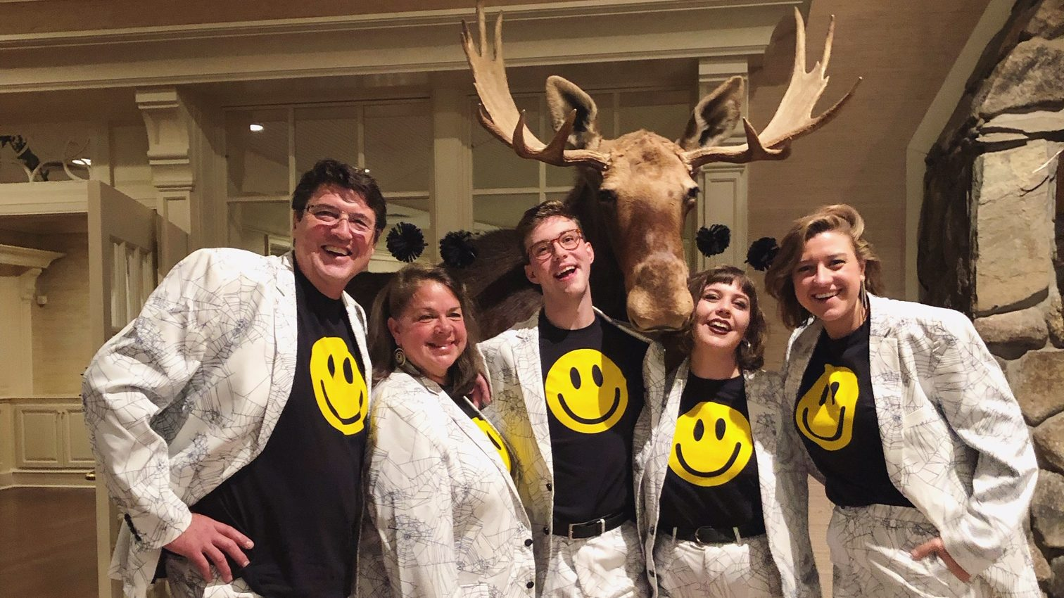 Image: The entire EWC team wearing spiderweb printed blazers, and a smiley face shirt underneath. The team is posing with a taxidermy moose.
