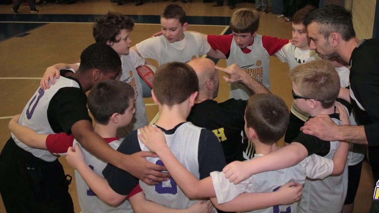 Image: young basketball players with their arms around each other in a huddle