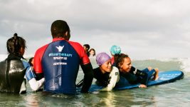 Image: two children in the ocean on a surfboard being held in place by a coach who sports a #SurfTherapy graphic on their shirt
