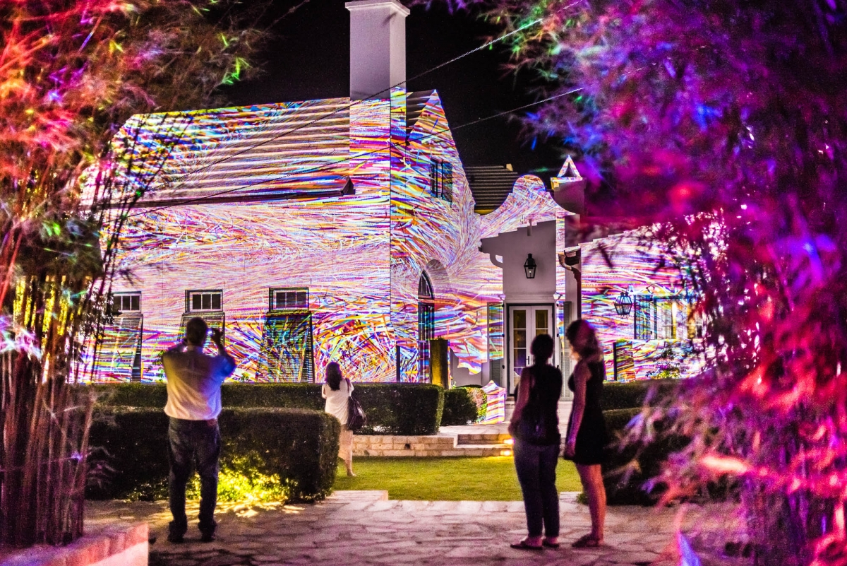 Image: digital graffiti projected on trees and house at Alys Beach. Viewers are taking photos