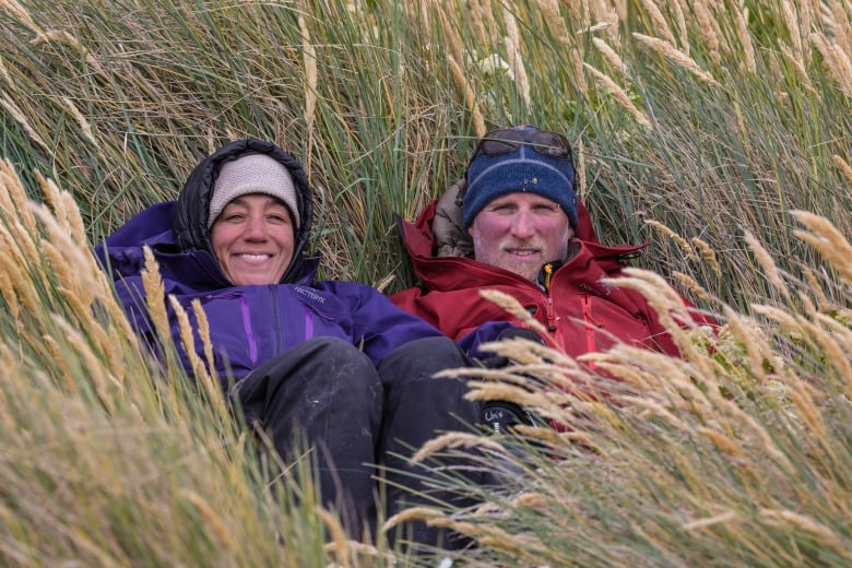 Image: Cristina Mittermeier and Paul Nicklen laying in tall grass smiling