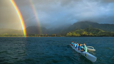 Image: outrigger canoe paddled by the US Mens Rafting team sits off the shore with a double rainbow behind them