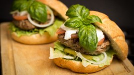 Image: A Hamburger with a huge basil sprig on it.
