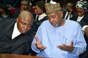 """Former national security adviser of ex-president Goodluck Jonathan, Sambo Dasuki (R), speaks with his lawyer Ahmed Raji, during his trial at the federal high court in Abuja, on September 1, 2015. Nigerian prosecutors on September 1, 2015 slapped a charge of unlawful possession of arms against Dasuki. Dasuki was arraigned on a """"one-count charge of being in possession of firearms without licence,"""" Prosecutor Mohammed Diri told the federal high court in Abuja. AFP PHOTO/STRINGER (Photo credit should read STRINGER/AFP/Getty Images)"""