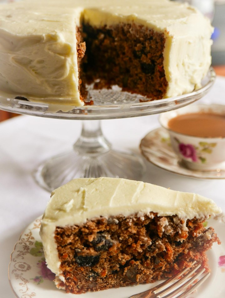 Carrot cake on a glass cake stand with a slice of cake on a plate next to it. A cup of tea is in the background
