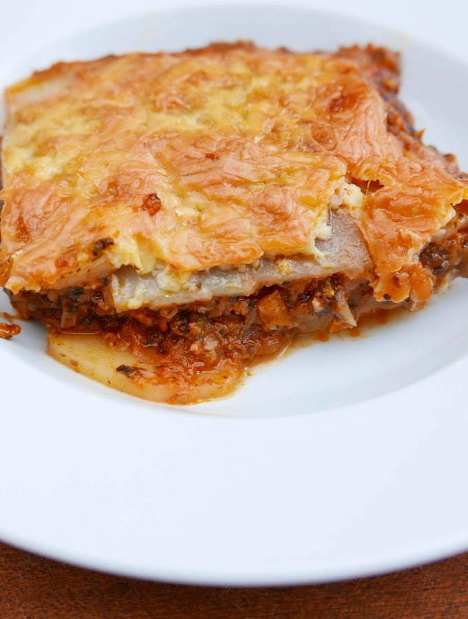 A portion of mince and potato gratin, with a thick layer of melted cheese in a white dish