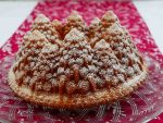 A Christmas Bundt cake in the shape of a circle of pine trees, dusted with icing sugar looking like snow. The cake is on a decorative glass plate on a red Christmas tablecloth.