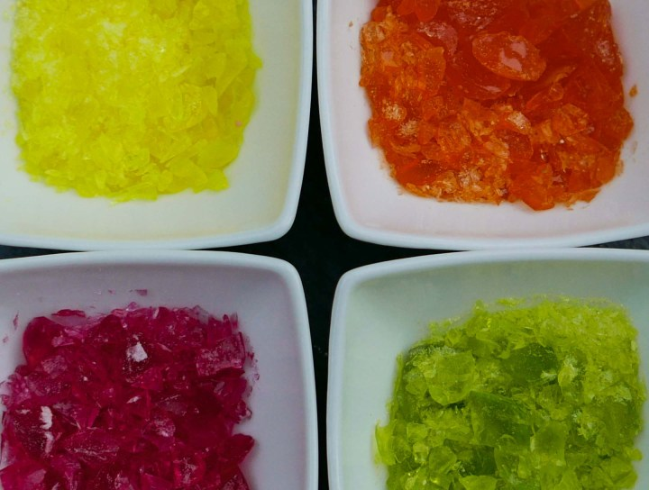 Yellow, red, orange, and green crushed boiled sweets in white dishes