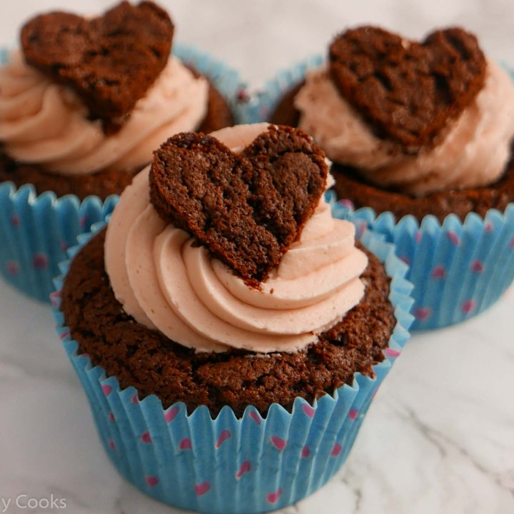 3 easy valentine cupcakes in a line. Chocolate flavour with pink buttercream and a heart on top