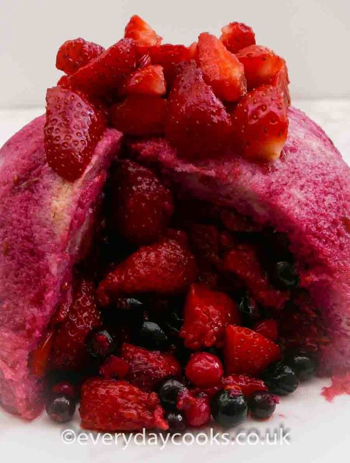 Summer Pudding full of berries with a slice taken.