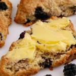 Buttered Blackberry Scones on a white plate with blackberries.