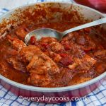 Chicken and Chorizo Casserole in a large frying pan with a serving spoon