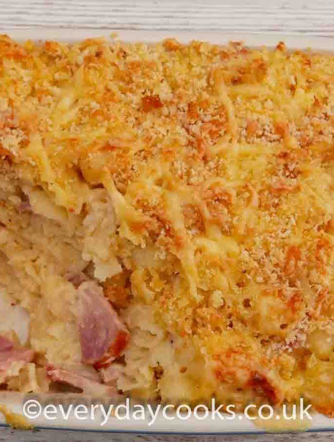 Macaroni Ham and Cheese, with a portion removed, in a gratin dish