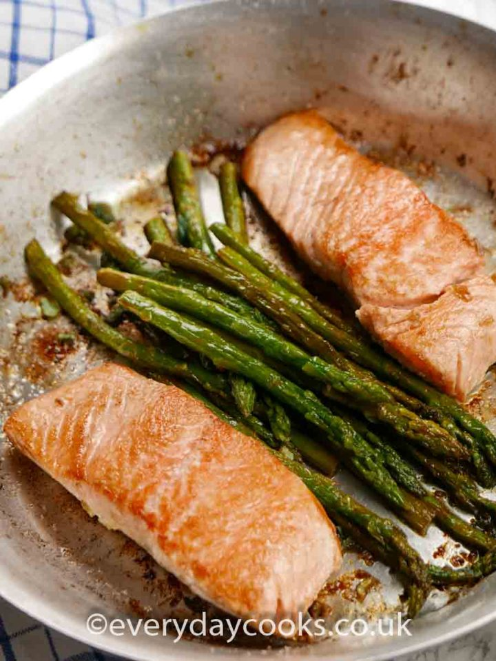 Pan-fried Lemon and Garlic Salmon with Asparagus in an aluminium frying pan.