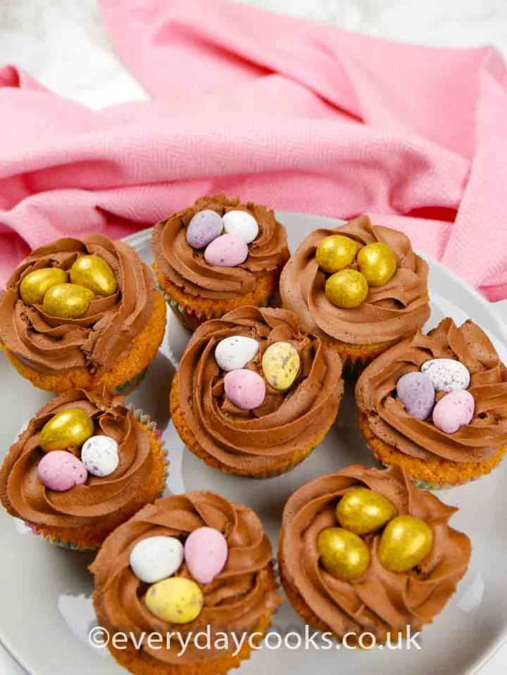 8 Easter Nest Cupcakes full of mini eggs on a grey plate