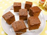 Squares of Gingerbread Traybake on a grey plate.