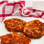 3 Sweetcorn Fritters on a white plate with a red cloth