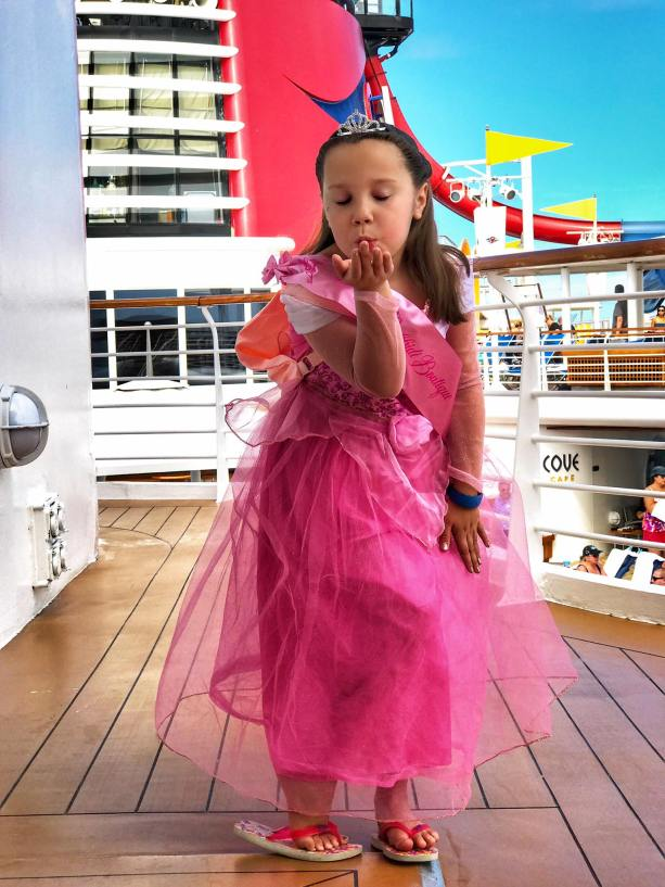 Little girl blowing a kiss on a Disney cruise