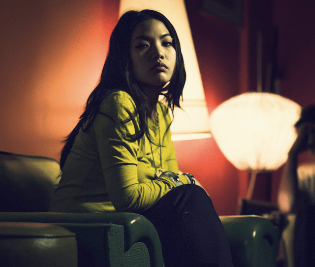 A Young Person Sitting In A Dimly Lit Room Gazing At The Camera