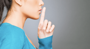 """Person holding a finger to their lips, saying """"Shh"""""""
