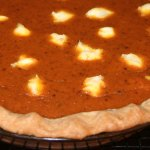 Close up of cream cheese pumpkin pie on a cooling rack.