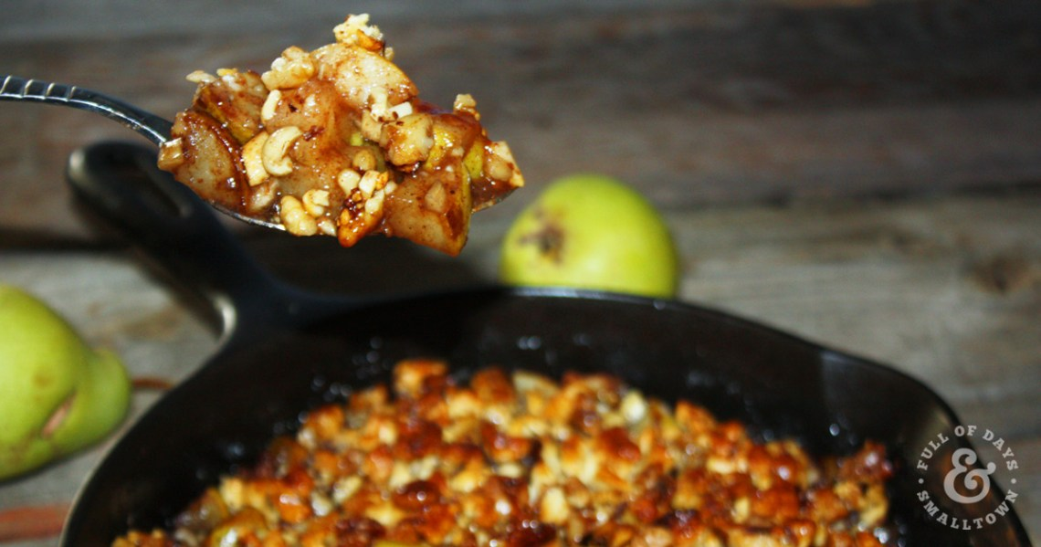 Cashew Walnut Pear Crisp in a Cast Iron Pan with a Spoon Scooping a Steaming Bite