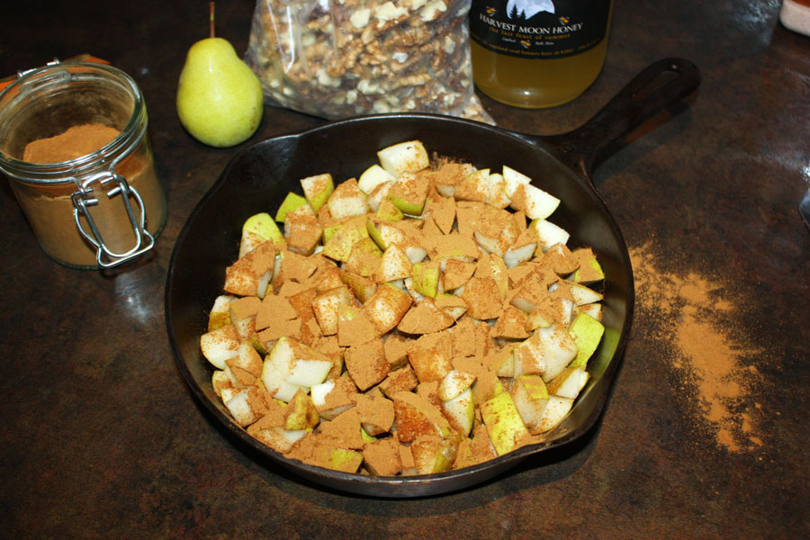 Pears in cast iron with spices sprinkled on top, ingredients in the background and cinnamon spilled on the counter