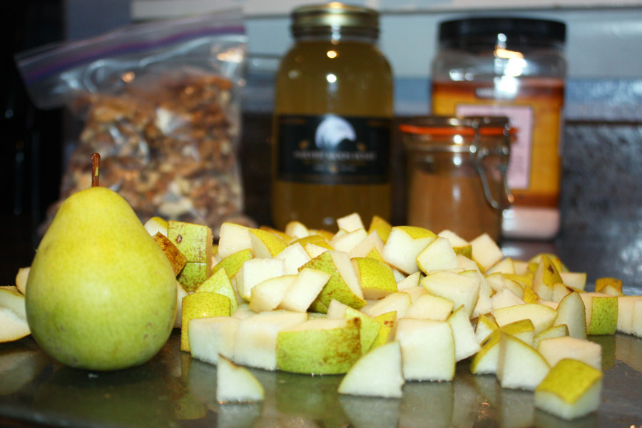 Chopped pears with ingredients for cashew walnut pear crisp in background