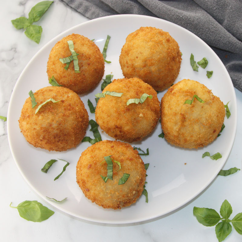 Crispy Fried Arancini Rice Balls garnished with Basil