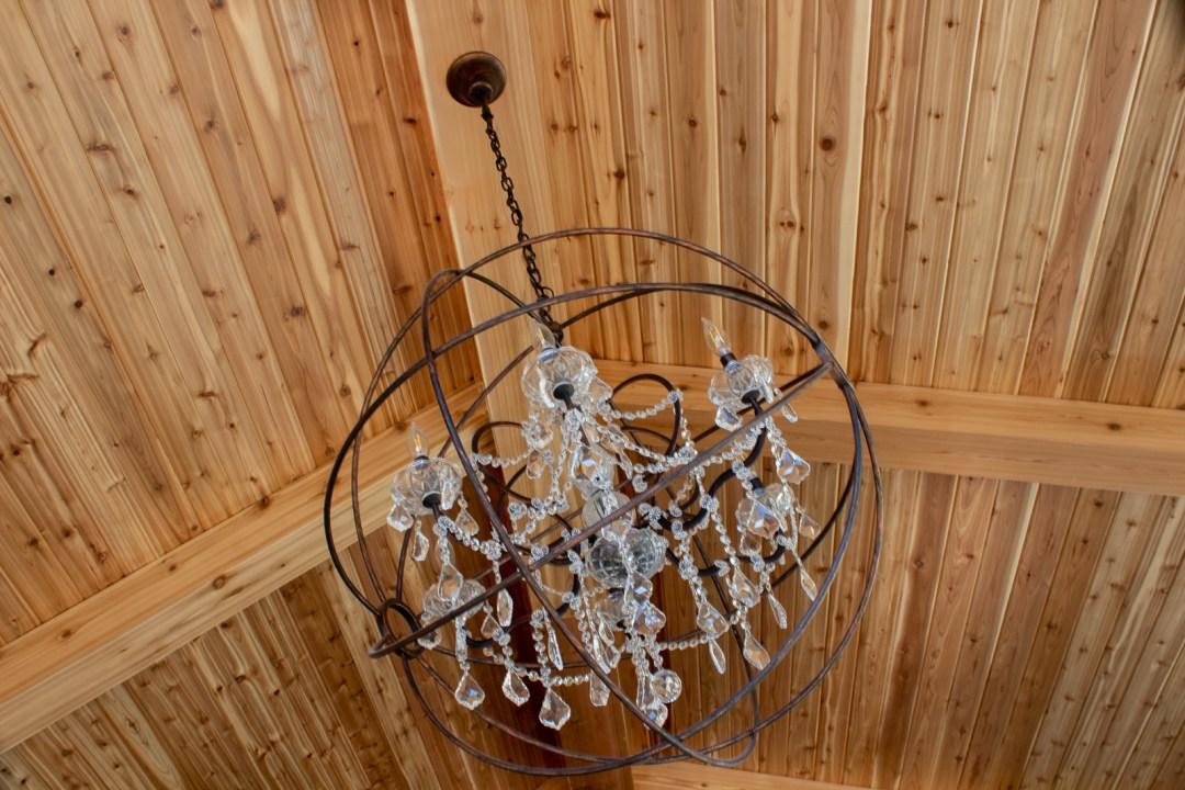 Crystal orb chandelier cedar wood stained ceiling