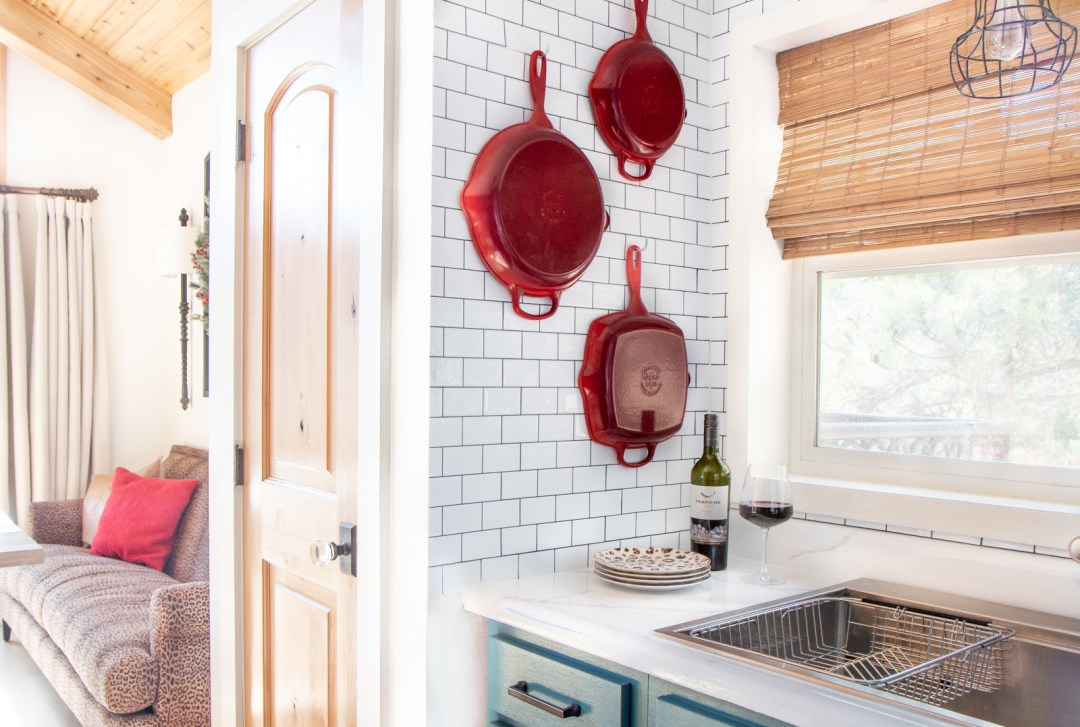 Red Le Creuset pans on wall