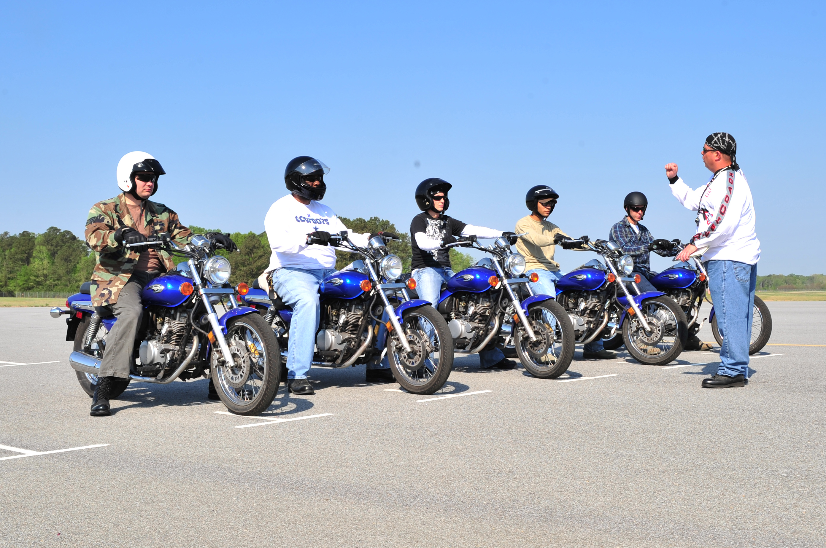 Trainer stands in front of a line of men sat on motorcycles