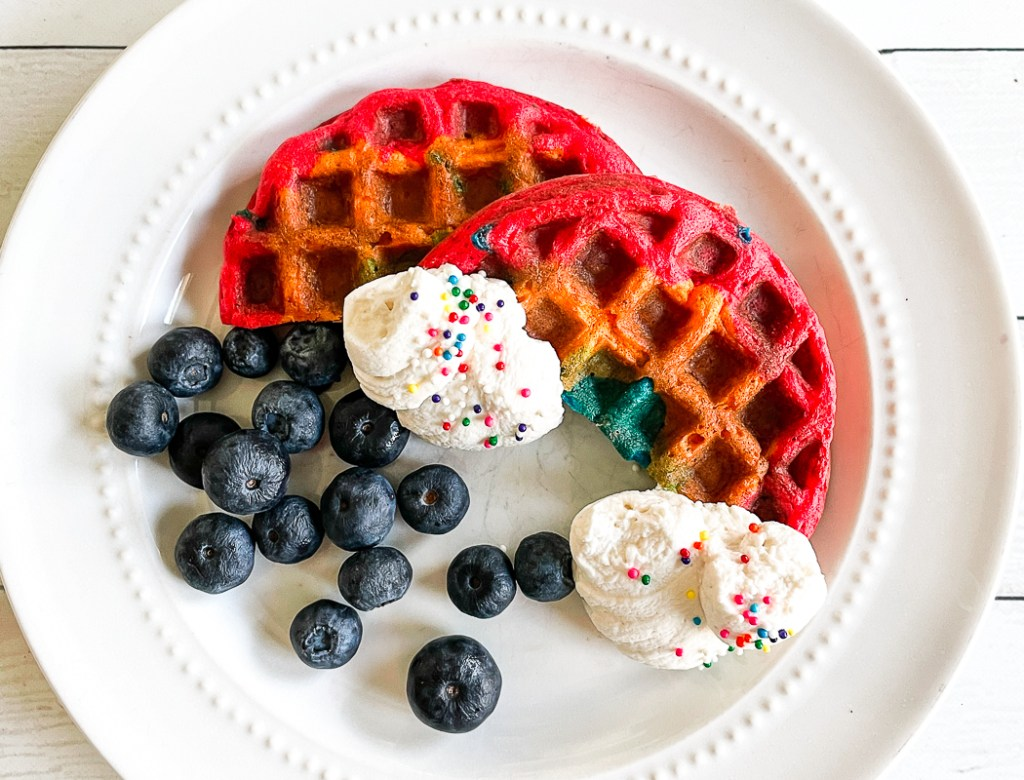 Rainbow Waffles Blueberries Whipped Cream on a plate