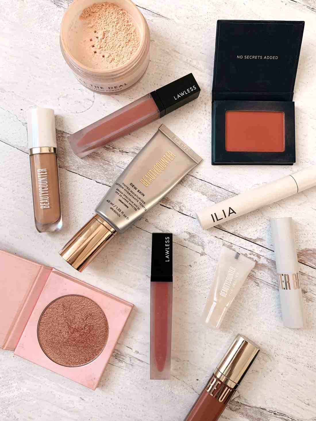 A variety of makeup products laid out on a white wood background.