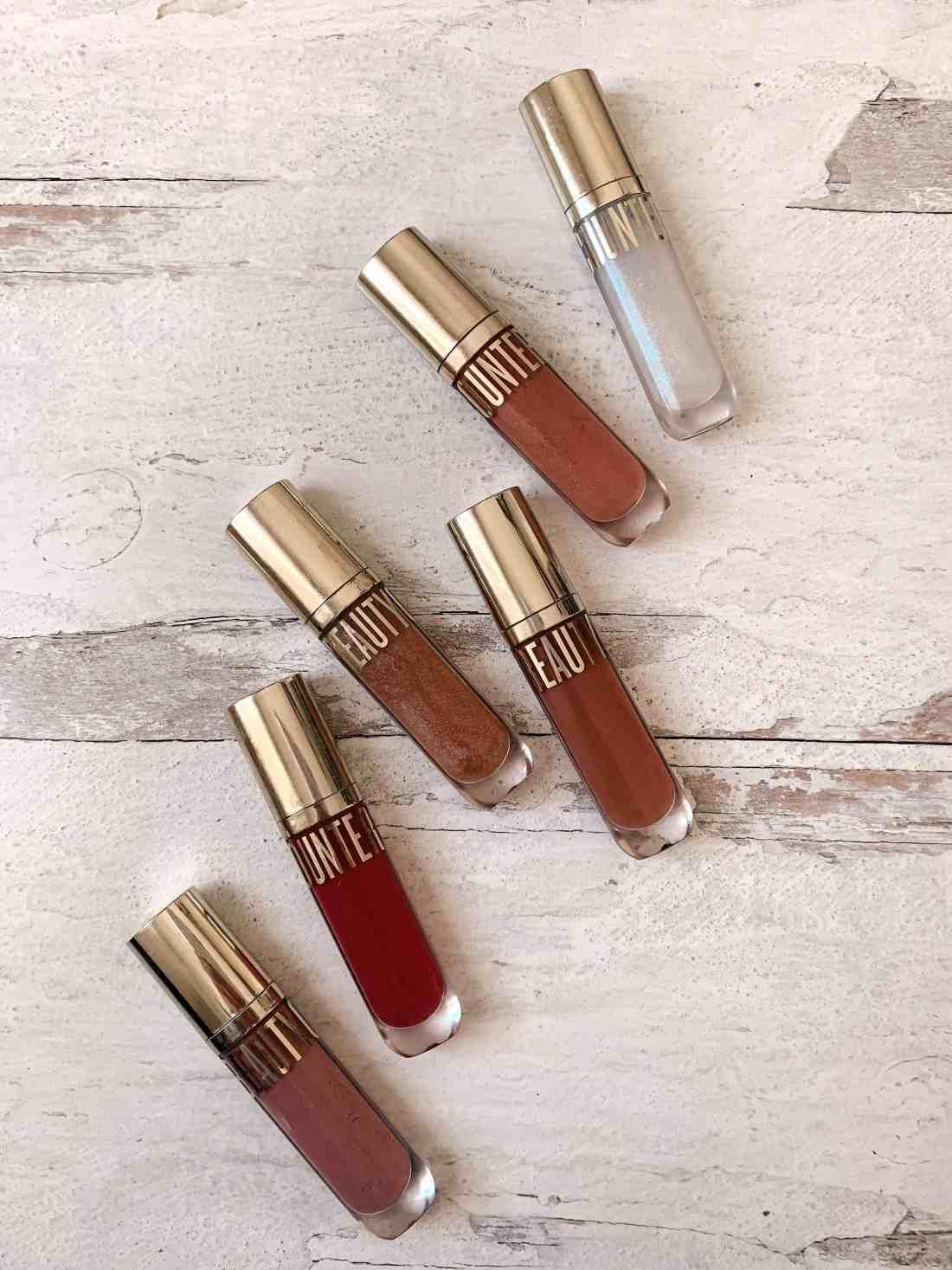 6 Beautycounter Beyond Gloss Lipglosses on a white wood background
