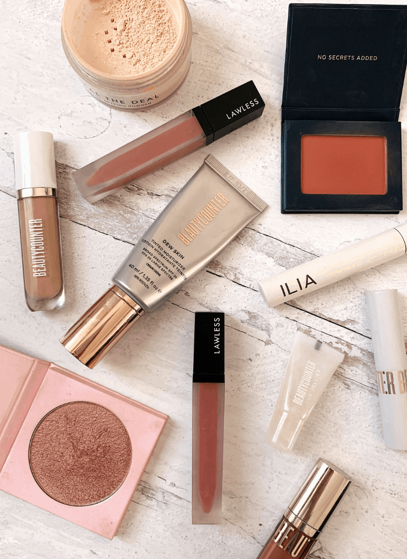 A variety of makeup products arranged on a white wooden background.