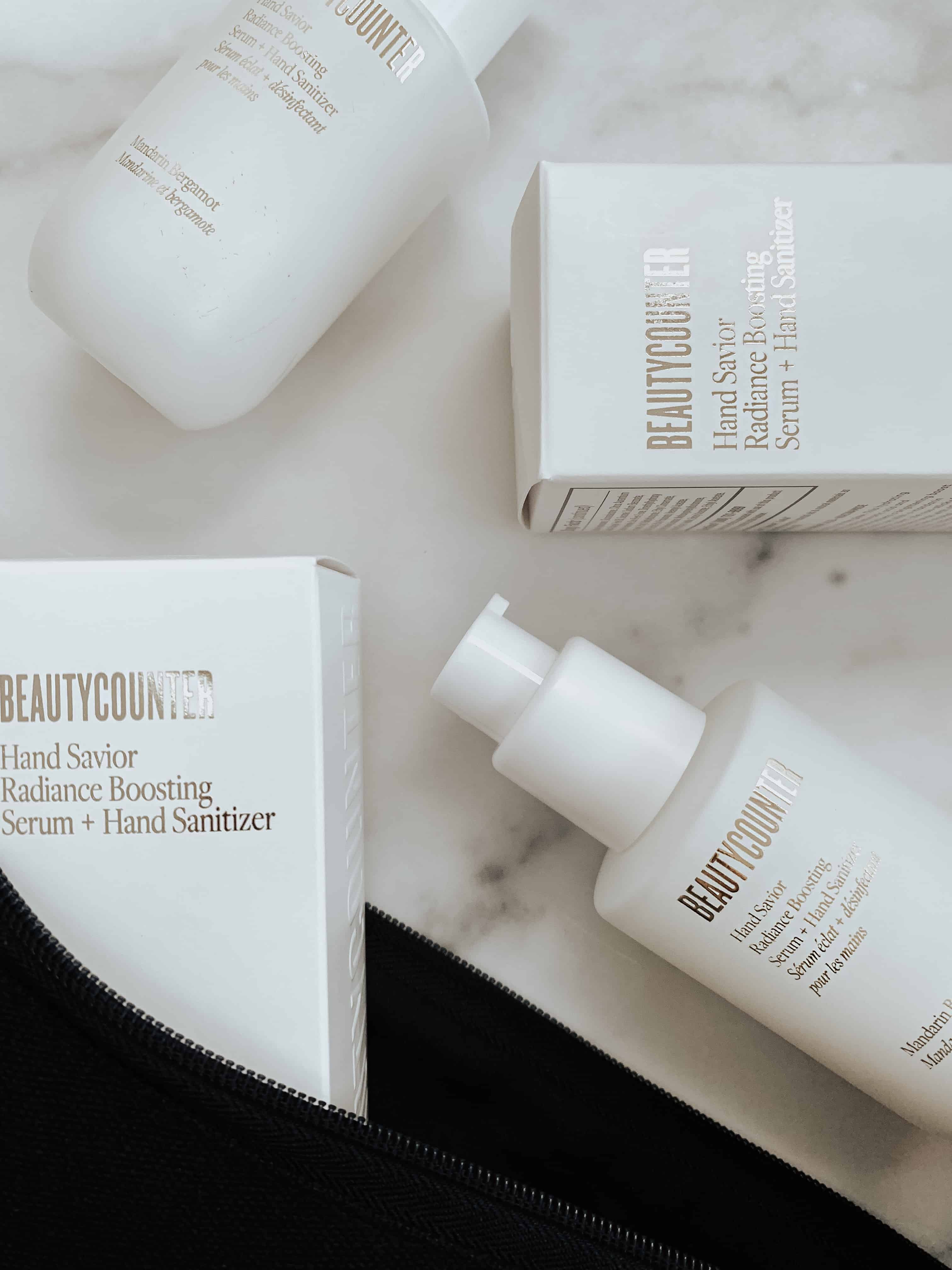 Two sets of Beautycounter's new Hand Savior Radiance Serum + Hand Sanitizer bottle and product packaging on a marble surface.
