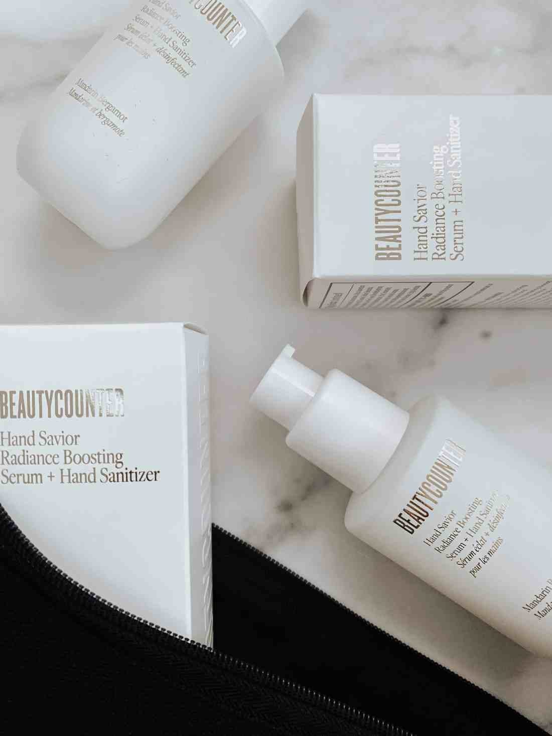 Two sets of Beautycounter's Hand Savior Radiance Serum + Hand Sanitizer laid out on a white marble surface.
