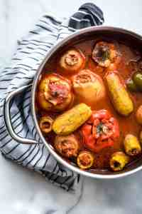 Stuffed vegetables in tomato broth in a large saucepan with a kitchen towel under the pan