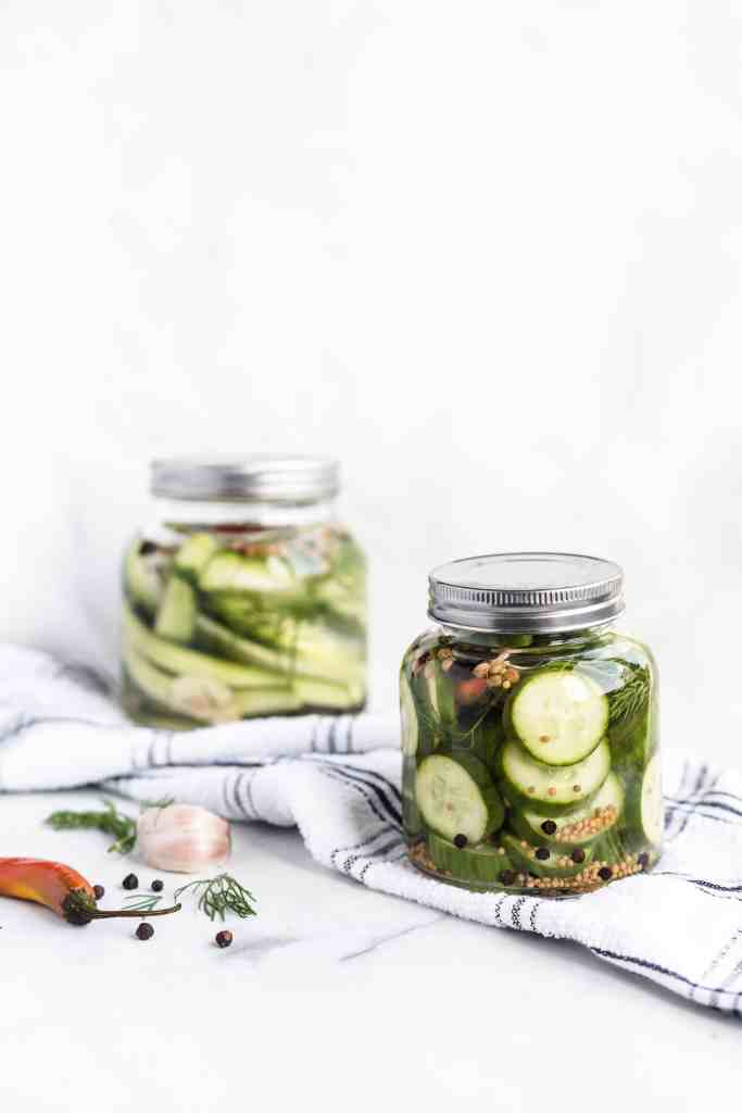 two jars full of dill pickles on a white kitchen towel