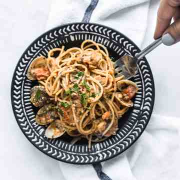 shrimp and clam pasta on a black plate with a forkful being taken out over a white kitchen towel