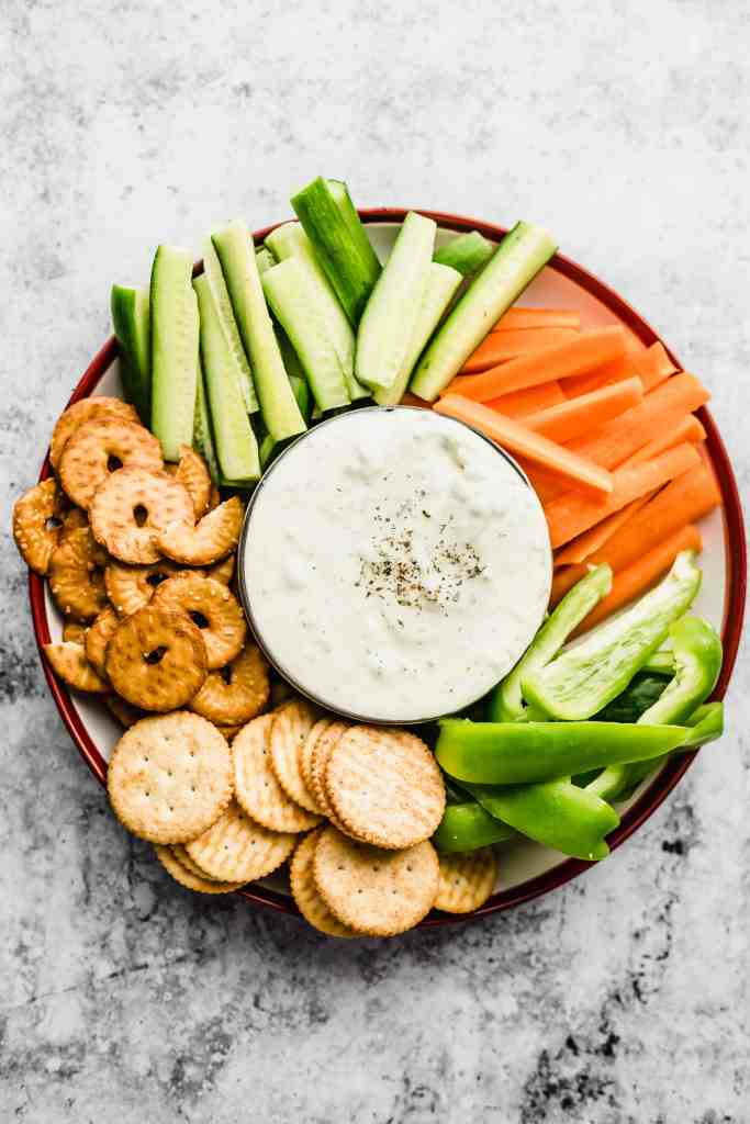 Plate with cut up carrots and cucumbers, crackers and pretzels with labneh dip in a bowl in the middle