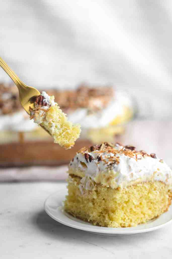 A fork with a bite of pineapple cake on it being taken out of a slice of pineapple cake on a white plate