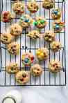 A black wire cooling rack with mini chocolate chip cookies on it, some with m&m's and a glass of milk at the bottom of the photo