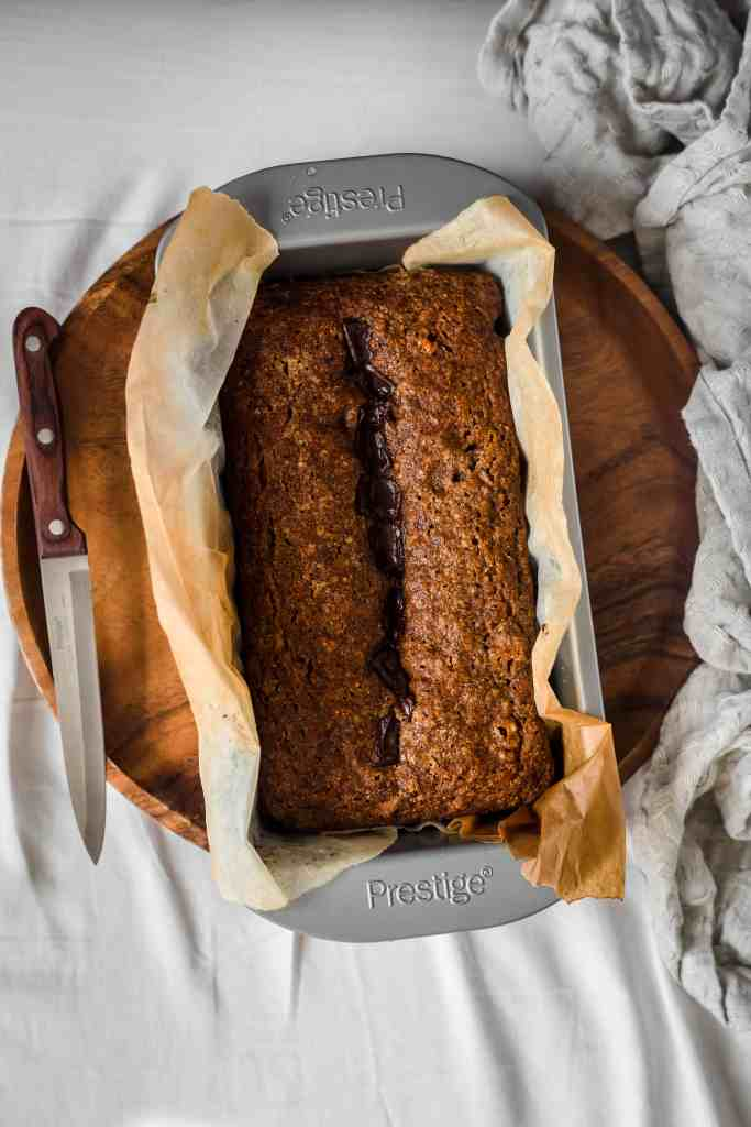 loaf of buckwheat banana bread in loaf pan with knife