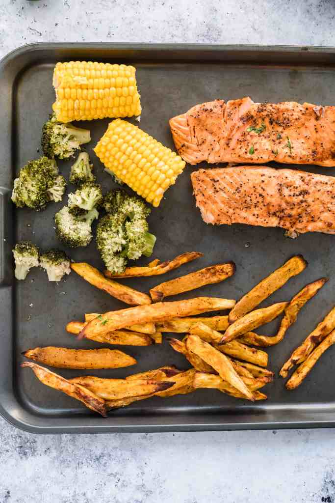 Air Fryer salmon on pan with corn, broccoli and sweet potato fries