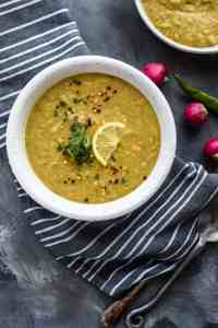 Middle Eastern lentil soup in two bowls with radishes on a kitchen towel